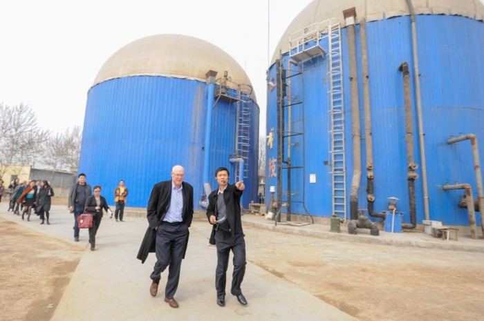 Paulson Institute Chairman Hank Paulson hears from Zhou Hanhua, owner of a pig farm, about the farm's waste-to-energy system and how it contributes to mitigating air pollution from ammonia