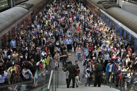 Paramilitary policemen direct passengers at a railway station during the traffic rush of the May Day holiday in Hefei