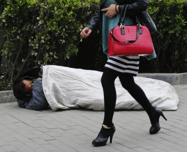 A woman walks past a homeless man sleeping on the street in Beijing