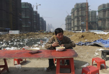 A migrant worker has his lunch near a construction site in Hefei